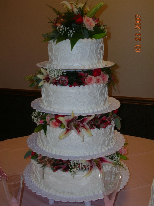 4 tiered round wedding cake iced with butter cream icing Scroll work